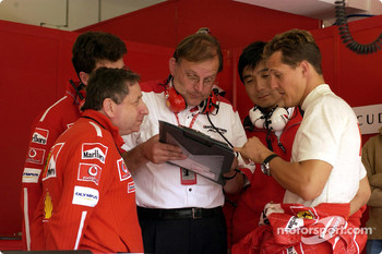 Jean Todt and Michael Schumacher discuss with Bridgestone technicians