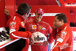Michael Schumacher discusses with Nigel Stepney and Jean Todt
