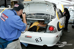 Team FBR/Trans Sport crew member hard at work in the trunk while being captured by photographers