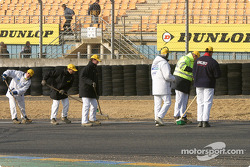 Corner workers clean up the track before the session