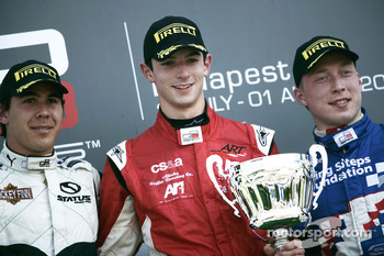 Alexander Rossi celebrates victory on the podium with Robert Wickens and Dean Smith