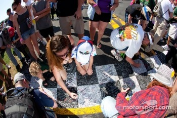 Fans sign the start-finish line