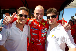 GT pole winner Gianmaria Bruni celebrates with teammates Giancarlo Fisichella and Pierre Kaffer