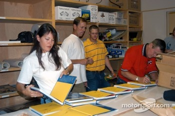 Jeri, Johnny and Bobby Unser and Jason Tanner signing copies of Gordon Kirby's new