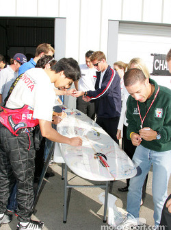 Tora Takagi and Tony Kanaan sign a surfboard