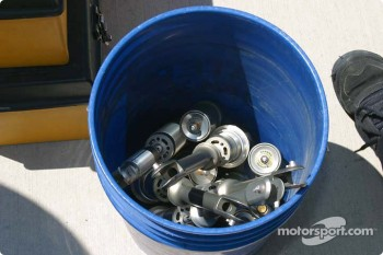 A bucket full of shocks sit in the pit lane