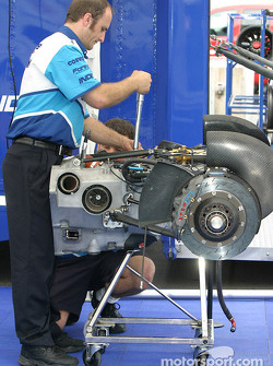 Forsythe Championship Racing crew members prepare rear suspension