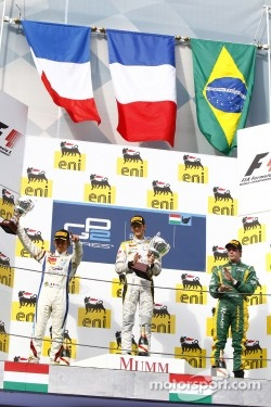 Romain Grosjean celebrates his victory on the podium with Charles Pic and Luiz Razia