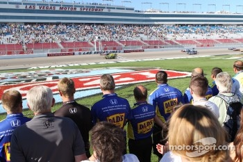 Pit crews line pit road as drivers complete a five lap tribute to Dan Wheldon
