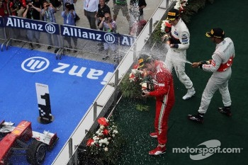Race winner Fernando Alonso, Ferrari celebrates with the champagne with third placed Lewis Hamilton, McLaren and second placed Sergio Perez, Sauber on the podium