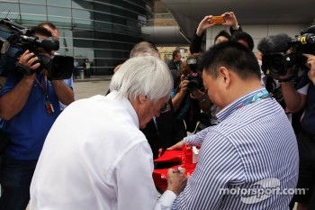 Bernie Ecclestone, CEO Formula One Group, signs autographs for the fans