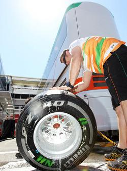 Sahara Force India F1 Team mechanic washes a Pirelli tyre