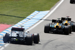 Lewis Hamilton, McLaren suffers a puncture as Heikki Kovalainen, Caterham and team mate Vitaly Petrov, Caterham battle for position