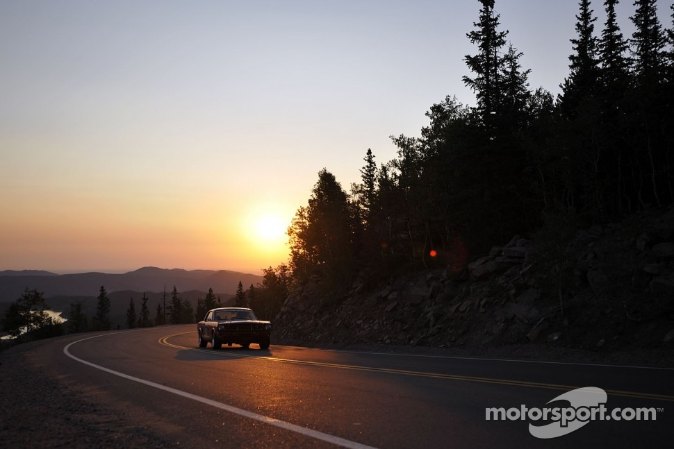 The sun rises over a vintage Ford Mustang