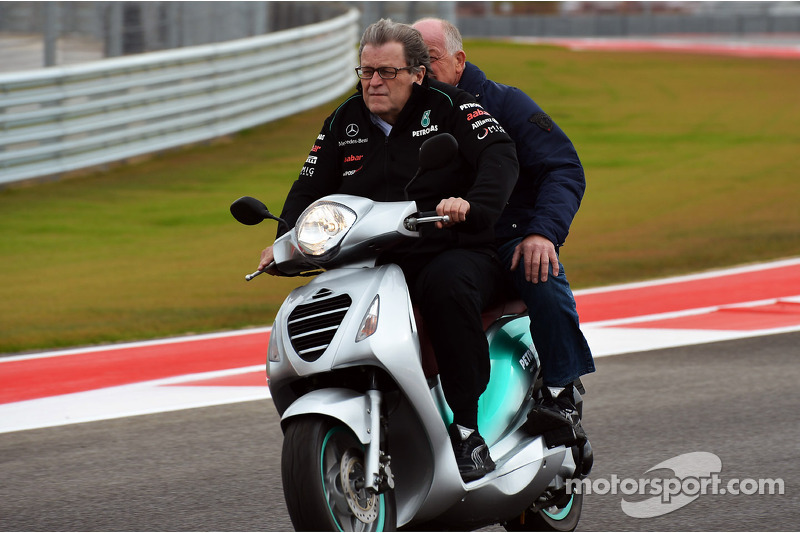 Norbert Haug, head of Mercedes GP, rides the circuit on a moped