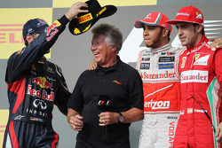 The podium: Sebastian Vettel, Red Bull Racing, second; Mario Andretti, Lewis Hamilton, McLaren, race winner; Fernando Alonso, Ferrari, third
