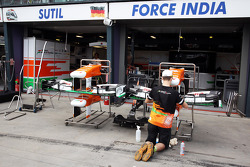 Sahara Force India F1 Team mechanic with Sahara Force India F1 VJM06 front wings outside the pit garages