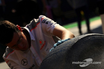 Pirelli tyre being washed by a McLaren mechanic