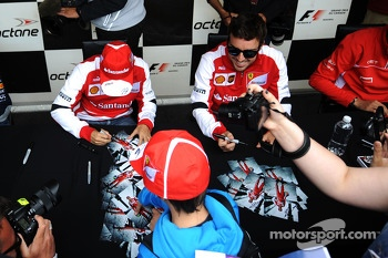 (L to R): Felipe Massa, Ferrari and Fernando Alonso, Ferrari sign autographs for the fans