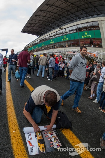 Fan rolling up signed Corvette poster at Le Mans