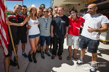 Rui Aguas, Kamui Kobayashi and AF Corse team members proudly pose with a charming flag girl
