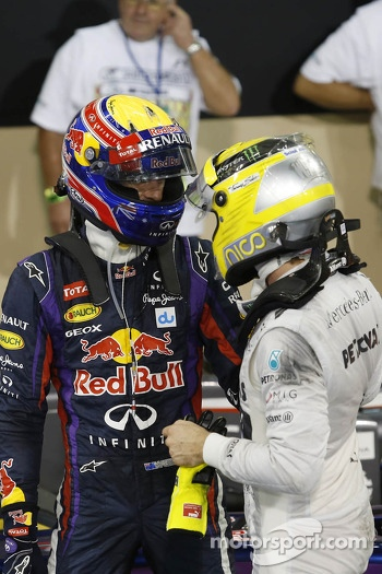 (L to R): Mark Webber, Red Bull Racing celebrates his pole position in parc ferme with Nico Rosberg, Mercedes AMG F1