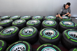 A Mercedes F1 GP crew member works on tires