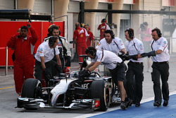 The smoking Sauber C33 of Adrian Sutil, Sauber is pushed down the pit lane by mechanics