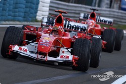 Race winner Michael Schumacher and Rubens Barrichello arrive in Parc Fermé