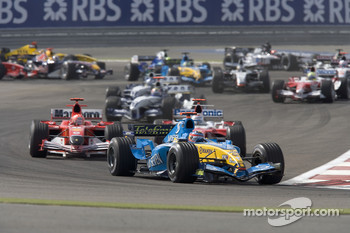 First corner: Fernando Alonso leads Michael Schumacher