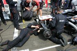 McLaren team members repair damage on the front end of Juan Pablo Montoya's car on the starting grid