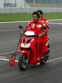 Ferrari team members measure the track