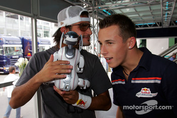 Vitantonio Liuzzi and Christian Klien play with a Sony Aibo robot dog