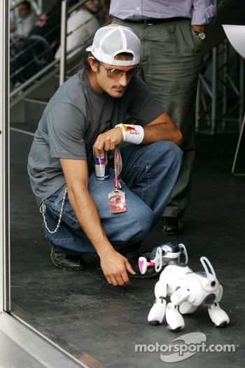 Vitantonio Liuzzi plays with a Sony Aibo robot dog