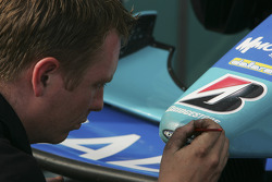 Crew member works on the parintwork on the car of Nelson A. Piquet