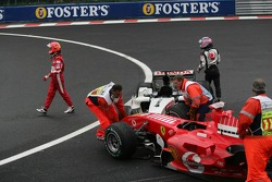 Michael Schumacher and Takuma Sato walk back to the pits