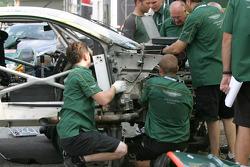 Aston Martin Racing crew members work on the wrecked #57 Aston Martin DB9