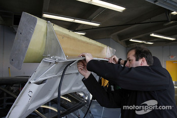 NASCAR engineers mount a rear wing on the NASCAR car of tomorrow test car