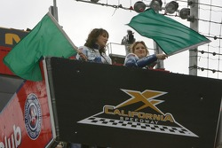 Haylie and Hilary Duff practice waving the green flags prior to the start