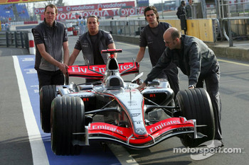 McLaren Mercedes team members push car to pits