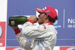 Lewis Hamilton takes a sip of champagne