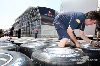 A Red Bull Racing crew member marking Michelin tires in front of the Energy Station