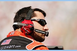Tony Stewart listens to radio communication between Ricky Rudd and the No. 20 Home Depot crew after exiting the driver's seat of his Chevrolet