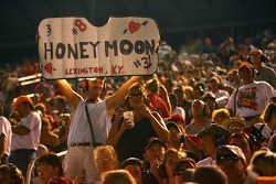 Honeymooners hold up a sign