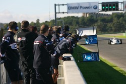 Formula BMW Drivers and team members watch Marco Holzer test the BMW Sauber F1.06, as his prize for winning the 2005 Formula BMW Final