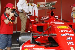 A young photographer takes pictures of Ferrari's Formula 1 car