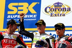 Troy Bayliss in second place, James Toseland in first place, and Noriyuki Haga acknowledge the crowd on the podium