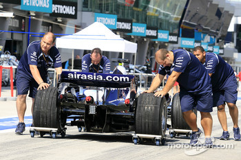 Williams F1 team members push car on pitlane