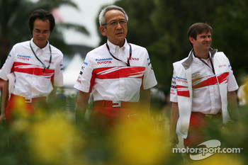 Team Principal Tsutomu Tomita arrives at Sepang flanked by engineers