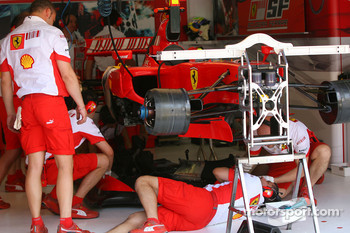 Scuderia Ferrari team members tune their car